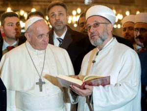 "In this photo provided by Vatican newspaper L'Osservatore Romano, Grand Mufti of Istanbul, Rahmi Yaran, right, shows Pope Francis the Quran, the Muslim holy book, at the Sultan Ahmet mosque in Istanbul, Turkey,  Saturday, Nov. 29, 2014. Meeting with Turkish leaders in the capital Ankara a day earlier, Francis urged Muslim leaders to condemn the ""barbaric violence"" being committed in Islam's name against religious minorities in Iraq and Syria. (AP Photo/L'Osservatore Romano)"